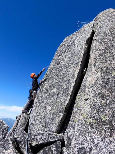 The standard way to surmount the summit is to climb an offwidth (5.7 to 5.9, depending on source). There is no bolt on the top of the summit block, so the safest way down from the top of the block is to sling the horn at the top of the offwidth, lower, and then flip the sling off of the horn as Will is doing in the photo.
