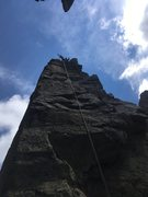 View from the saddle between Cake and Candle of climbers atop Candle rigging to rappel.
