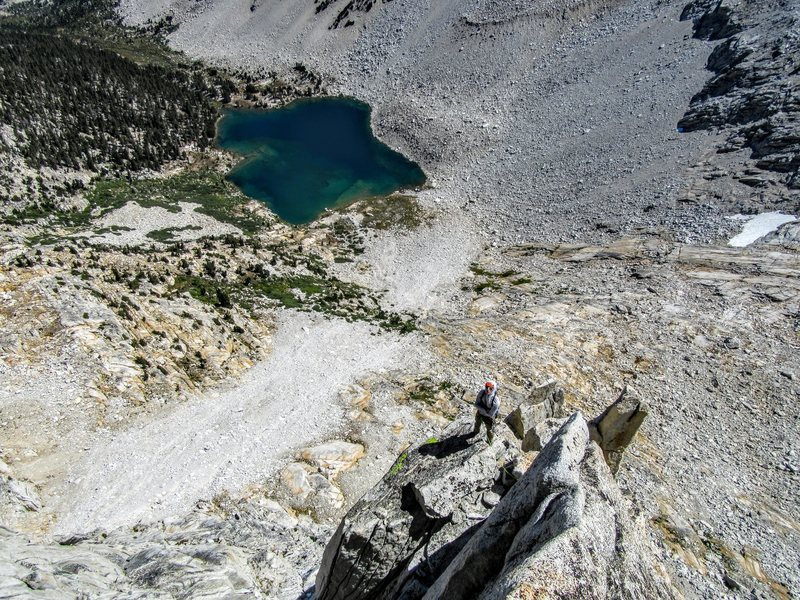 Neil Kauffman enjoying the exposure on P5 of the North Buttress. Third Recess Lake below.