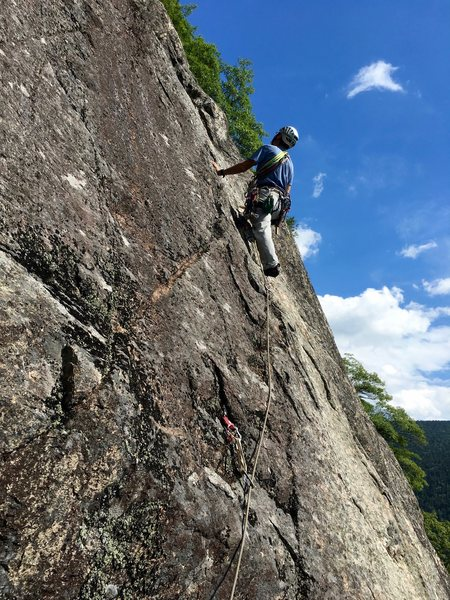 "RH leading P1 up the diagonal dike (Photo taken from the P1 ""Mice & Men"" belay stance)"