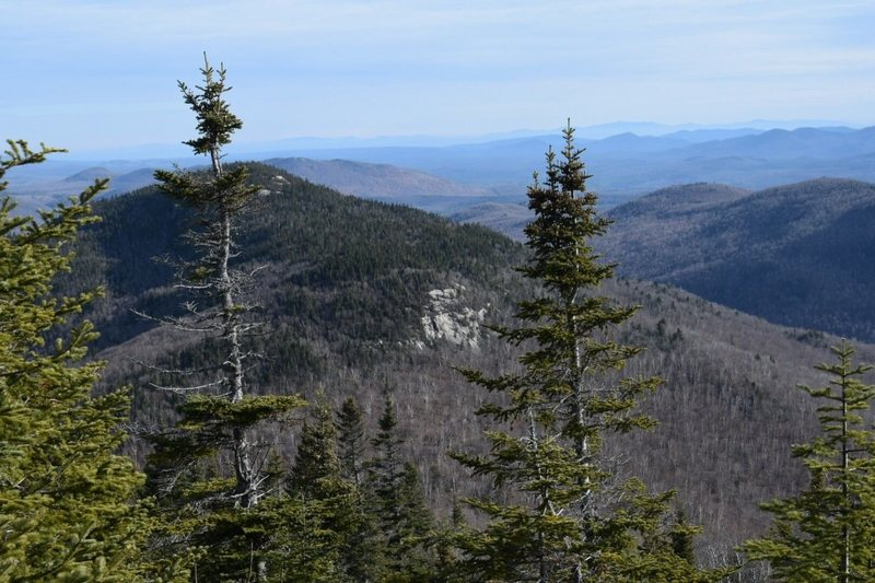Looking East from the fire tower.  The close, larger piece of rock is The Slab.  Higher up are West Crag and South Crag. This shot shows the sharp delineation between the hardwood forest of the lower slopes (good 'whacking) and the upper conifers (ugh.)
