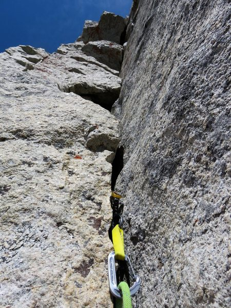 Pitch 5. The harder (5.9) but better option is to climb cracks in the summit block right of the leaning flake.