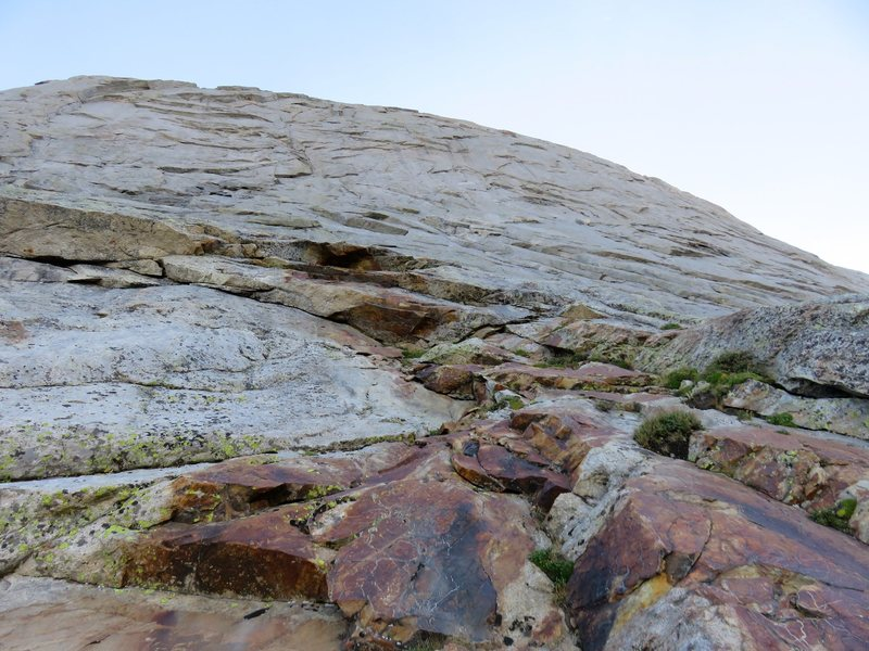 The start of Pitch 1, about 100 feet up at an arching, vegetated ledge with red stone above it.