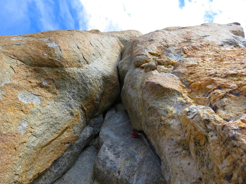 Looking up at the start of Pitch 2. This is the crux of the pitch but the feet are good and there is a piton just above the bulge that you can clip before making a committing move if you know to look for the piton. But the piton is old, so I backed it up with a 0.75 cam.