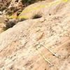 Second bolt anchors on the approach. These are not the most useful things in the world on the hike up. On the way down, however, they are key. Once you climb the slab in the middle of the second section of cliffs (carin at the top). There is tat on a bush next to the carin, and the rap anchors are about 15 feet west of that. The rappel is kind of hard, so be ready for your backpack to pull you over.