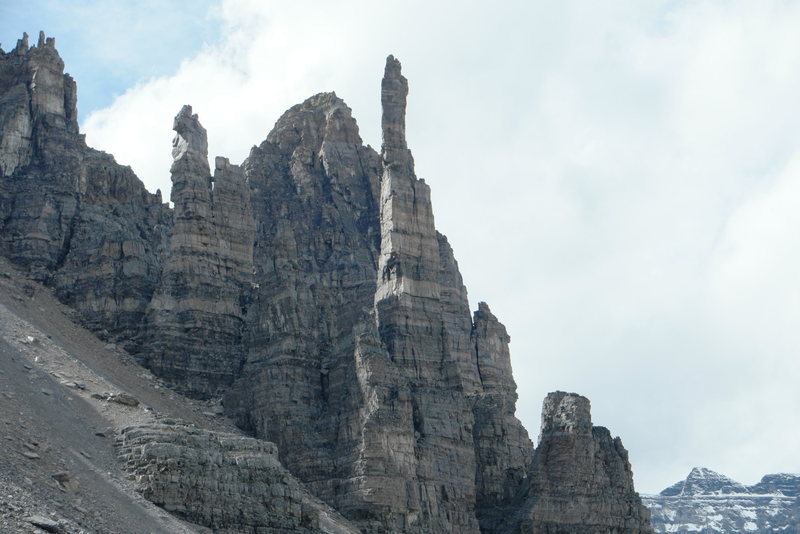 Grand sentinel spire with climbers near top of cardiac arête.