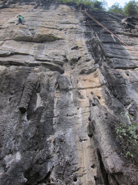 "The climber is on ""Where's the Jug?"". There are two routes through the mini-roof. This route route starts just left of the black streak on the right. The orange rope is on a fifth route up the tufa."
