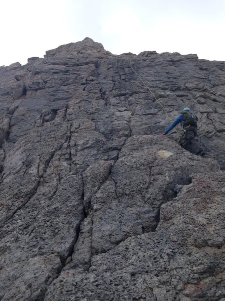 Climber seconding the 8th pitch. First pitch off the big ledge after the walk