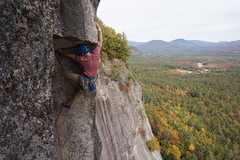 Pulling the iconic roof after the stemming corner on The Prow at Cathedral, N. Conway, N.H.
