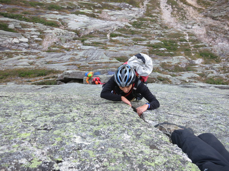 Seconding the crack pitch with the belay ledge visible below.