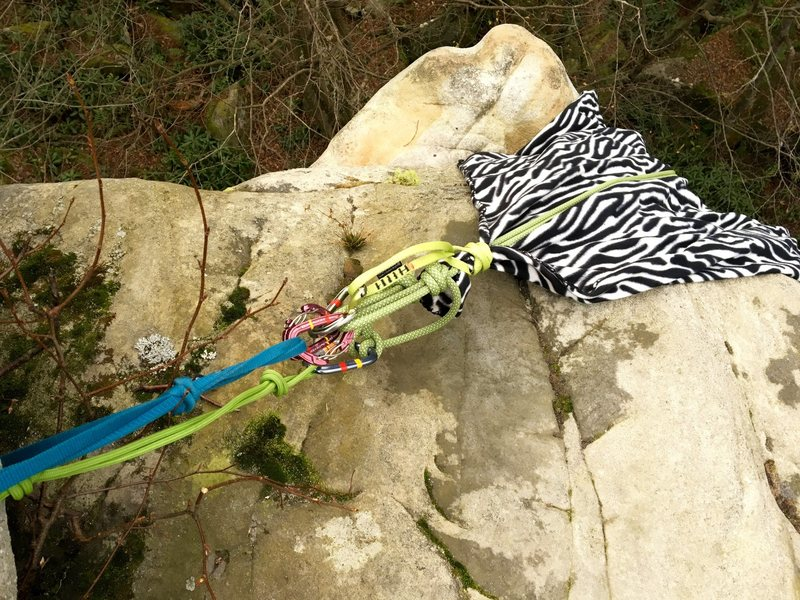 """My super jive ass anchor setup for TR solo. The rock is mega abrasive here... that is a $2 Walmart fleece blanket that I secured to the rope. There is another cheap-o blanket out of view that is protecting the blue and green cordolettes. FYI (so you can know WTF you are looking at) despite the padding I was still concerned about the cordolettes. Thus, the blue is the """"primary,"""" each side of the rope is secured via an overhand on a bight to a twingate biner on the blue webbing. In between these two OH on a bight knots is about two feet of slack, in the middle of this slack the rope is clove hitched to a locking biner on the green cord. Thus, if the blue were to fail while I was hanging on it, I would fall about a foot and this would serve as my """"warning"""" that something is really, really wrong up there."""