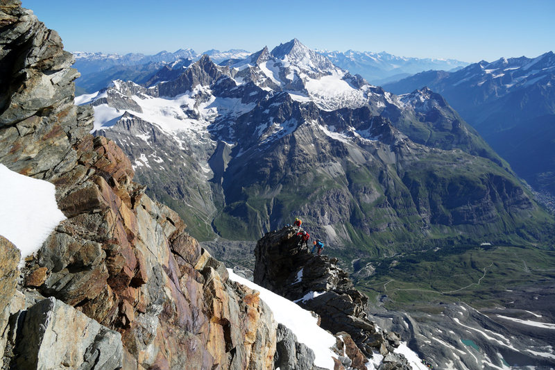 Climbers on the Shoulder Ridge with Weisshorn Group peaks seen in the background.