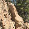 Brice climbing up alternate start under the pillar, belayer at base below.
