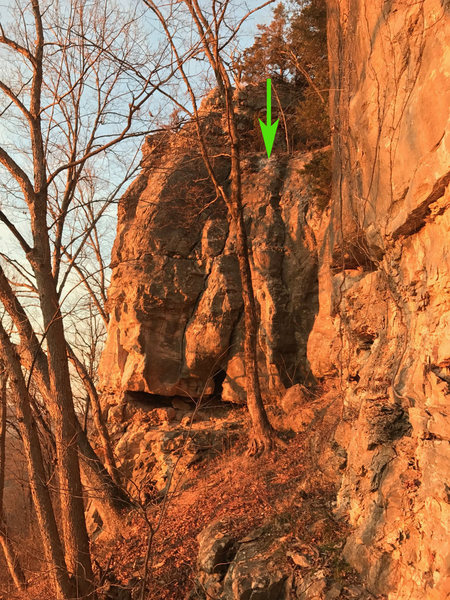 As of 12/30/16 a new 2 bolt anchor has been installed at the location of the arrow.  This is between the routes YO-YO and Maplewood Crack.  The placement should service most/all trad lines on the wall left of the cave with some moderate traversing to get in position.