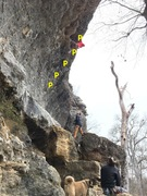 Climber is traversing over the orange cave and just below the anchors