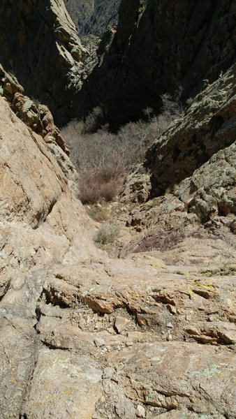 """Looking down at where the route starts. It is """"right around the corner"""" East from Hummingbird Saddle. Go through some bushes to a flatter ledge to get climbing shoes on."""