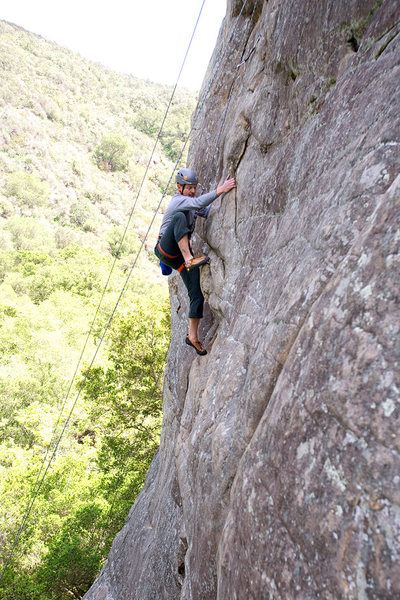 Past the crux, Ian makes a high step towards easier ground on Orangahang at San Ysidro.