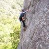 Past the crux, Ian makes a high step towards easier ground on Orangahang at San Ysidro.