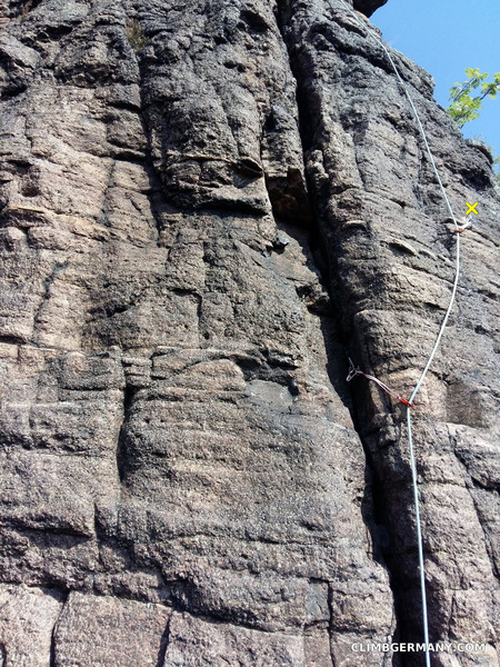 """Blockgrat, start of pitch 2. After stepping over from the tower onto the wall. Place pro while you still have one foot on the tower and one on the wall. """"X"""" marks the only bolt on the whole route, a nice glue in."""