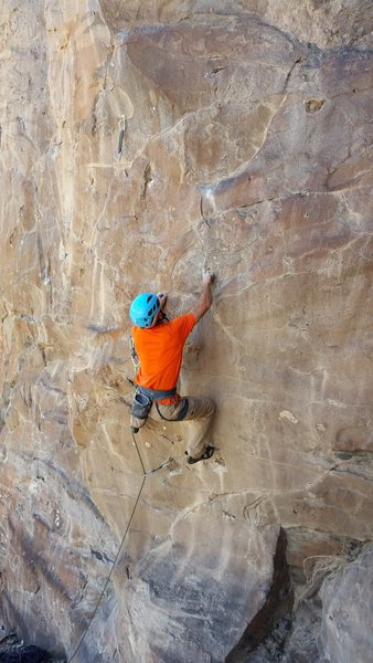Josh sets up for the final move of the first crux.