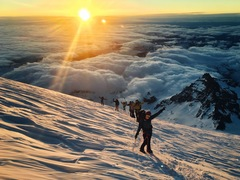 Climbers high on Rainier at sunrise after climbing the Ingraham Direct.