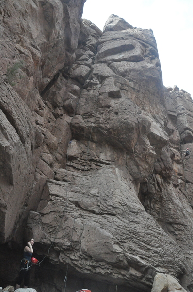 Route follows the crack in the left of this image, starting at roughly the climber about to clean the route.  Lefthand side of rope is over route, right hand is coming from anchors on Feast and Famine