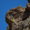 Possibly the block on the corner would be a good belay spot, 3 bolts into wall above it and the belayer could lean out and see what the leader is doing on the overhang, unfortunately posting the photo steps down the image quality, but if you click View full size then click on the photo you can see the piton and its shadow in the crack, the corner in red has been climbed many years ago,  Photo by Richard