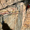 Starting the traverse on the first pitch of Alphonse, taken from the awkward hanging belay.