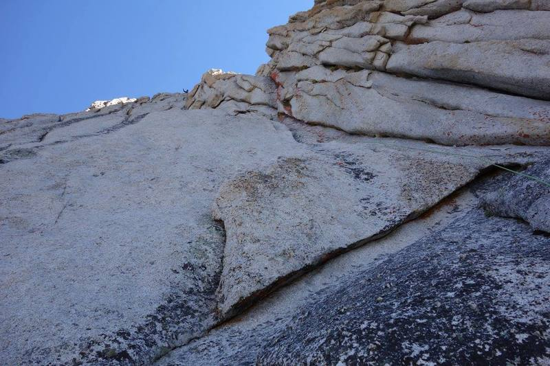 Alternate start to the crest--good for skipping a party that might be slowly pitching out the first pitches. Maybe 5.8+? Follow the left facing corner past bail slings. When the corner gets too steep, tension traverse a few feet left (C1) up to a steep but easy unprotectable runnel (PG). Continue up a full 60m rope length and belay ontop a buttress leading into the true crest. Another 30ft 5.5 pitch up the buttress joins the crest.