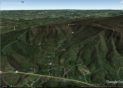 google earth view of the area, note faint cliff bands to the right and left of the pin