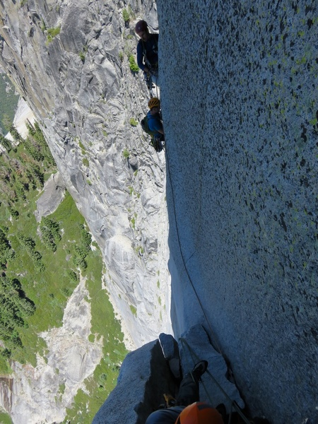 (Pitch 12 after Rockfall.) A view of the rope toss from above. I have started my lead of Pitch 13, and am looking down. My partner Sam is at the belay on the left and another climber (Alex) is doing the rope toss from the bolt in the C2 corner on the right. Yet another climber (Alister) is arriving at the bolt in the C2 corner. This pitch had taken awhile so we had a traffic jam of all three parties trying to get through it.