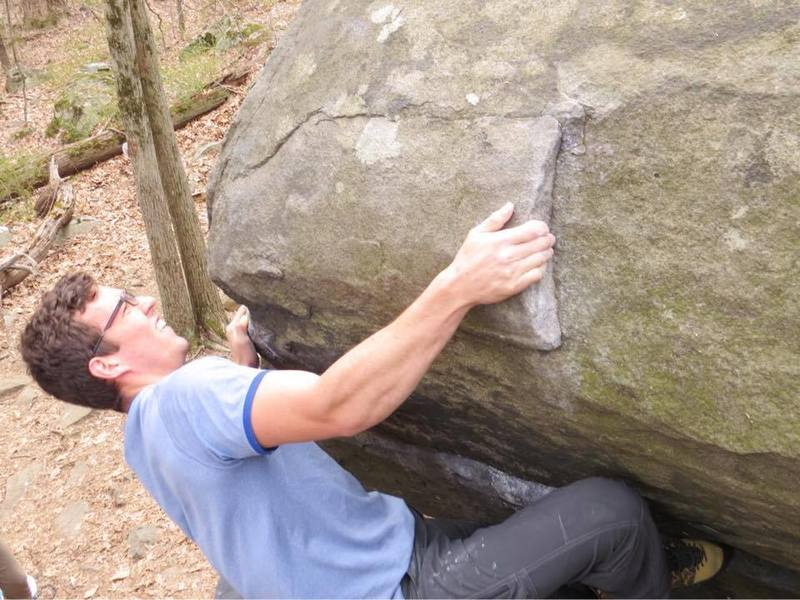 Latching onto the last real hold before the crux top out on the wave full