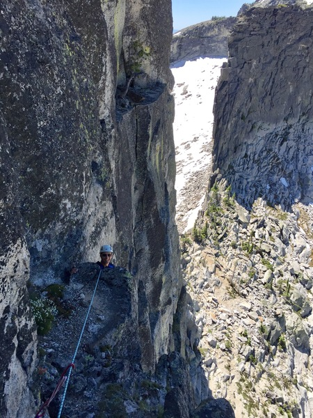 Dean moving out of the chimney top of pitch 2 onto large belay ledge