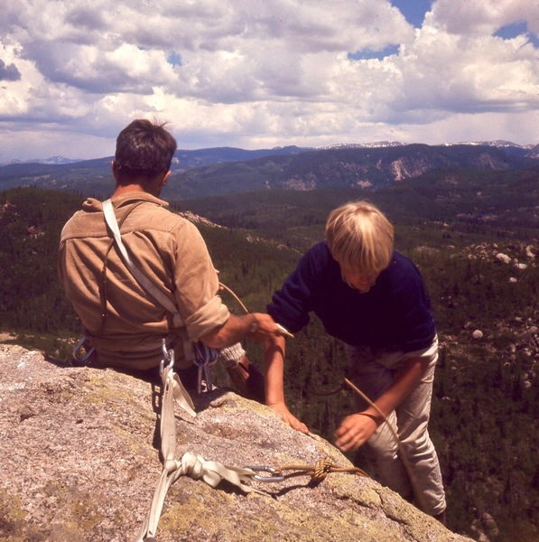 Ray Palmer belays John McClellan up the north side. The Zirkel Wilderness and continental divide are in the distance.