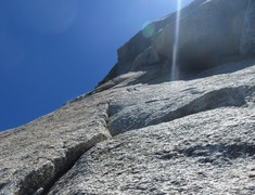 This fixed piton and the dihedral to the right is Fingergrip (5.8). Instead, go left after the 5.3 layback pitch (P3) to get to the fingertip traverse.
