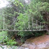 Rope bridge crossing the river between the road and the hillside leading up to Fluffy Kitten Wall.