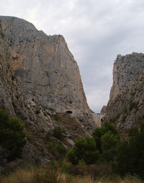 View of the buttress (left) from outside the canyon mouth.  The route is generally located above the tunnel mouth.