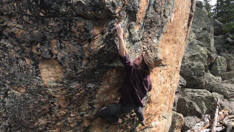 Gripping hard on the crux pinch of Walking Tall, V6.