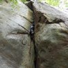 fighting through the slightly overhung fist crack to reach the thank-god traverse jug
