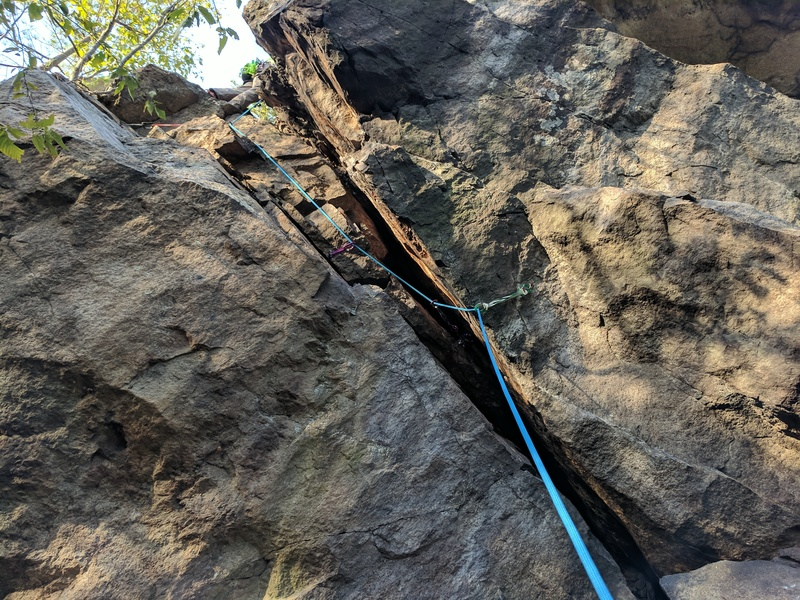 A tough 5.7 lead; this chimney may spit you out and leave scars. Wear a long sleeve shirt and pants. Optimal placement of gear on your harness and rope management are a must - this route is a squeeze!