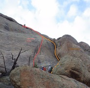 Looking up from the base of the climb. 2 climbers can be seen at the start. One climber is at the anchor.