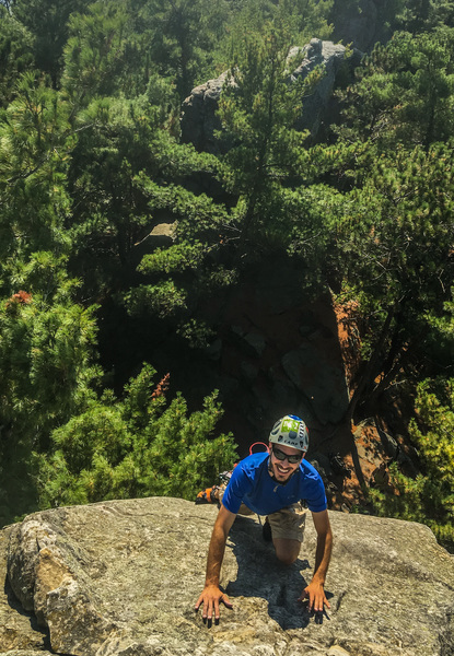 Justin all smiles as he tops out onto the best belay ledge in Wisconsin.