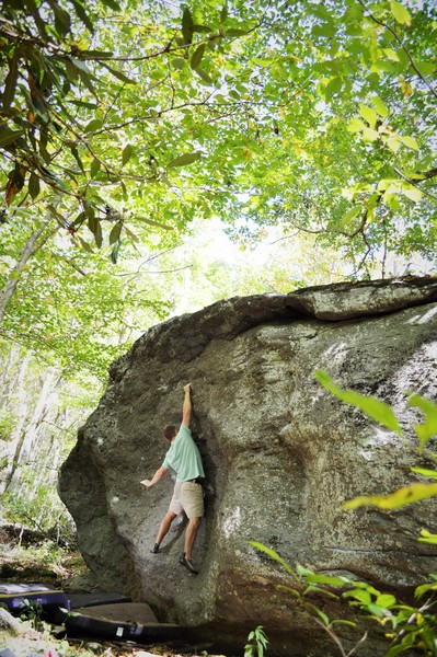 "Chris Grasinger standing tall on ""Salute"" at the Roadside Boulder, Left Boneyard, GHSP"