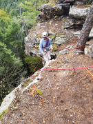 Setting up to rappel and place directional gear for top-rope.