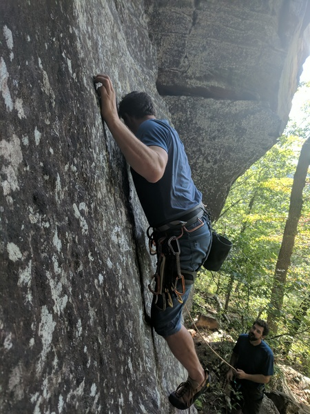 Jeff pulls onto the slab, which is actually the first crux.