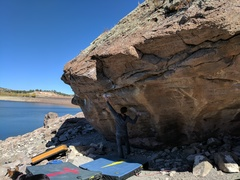 """Notice, the boulder has sunk about two to three feet and tilted downward on the westward side about 10° (i.e., it's steeper). Climber is 5'10"""" and easily reaches the sloper."""
