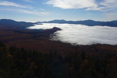 Looking down at the fall colors from atop the Main Cliff as the morning fog engulfs Birch Hill