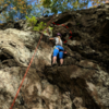 The route follows the rope, and the variation (dotted line) goes right of the small overhang/bulge just above climber's head. The right option is juggy with less protection. The straight option (left of the bulge) has slopers with more protection (and vegetation).