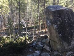 You can see the boulder and problem through the trees on the left from lll Vibrations.