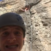 My belayer Sam pausing to take a selfie while I rest in the small cave midway up the climb.